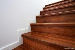 Lackierte Holztreppe vor weißer Wand