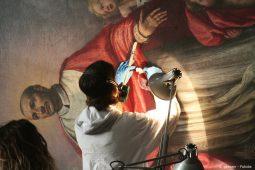 Ein Restaurateur arbeitet an einer Wandmalerei