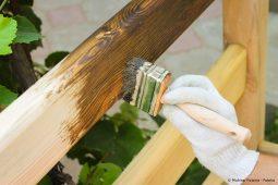 Ein Zaun wird mit einem Pinsel gestrichen