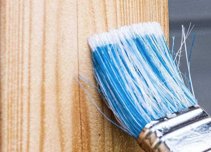 Pflege eines Holzfensters mit neuem Anstrich
