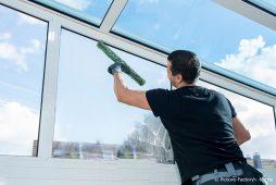 Professionelle Reinigungskraft pflegt Fenster