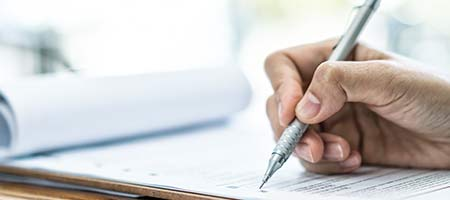 Hand mit Stift füllt Umzugscheckliste aus