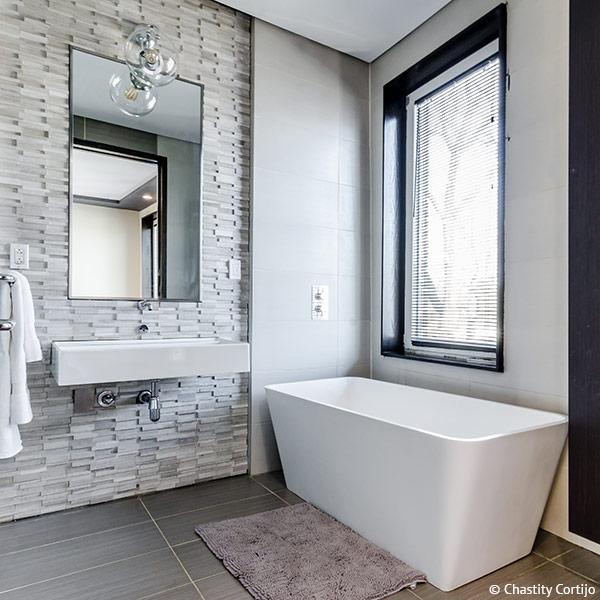 Eine Wand aus Naturstein lockert die Optik des Bads auf